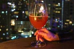 Kvinnligs hand som rymmer ett exponeringsglas av den röda coctailen på takstången med oskarp stads- nattsikt i bakgrunden fotografering för bildbyråer