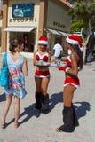 KvinnligSanta Claus erbjudande drinkar till turister arkivfoto