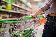 Kvinnligshoppare med trolleyen på supermarketen Arkivfoton