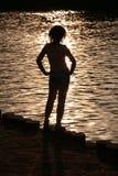 kvinnligsilhouettesolnedgång fotografering för bildbyråer