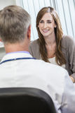 Kvinnligtålmodig och manligdoktor i ett kontor Arkivfoton