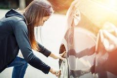 Kvinnligt ändrande gummihjul med hjulskiftnyckeln med solljus arkivbild