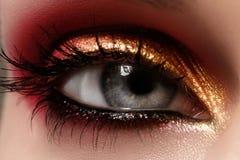 Kvinnligt öga för Closeup med ljust smink för mode Härlig skinande guld, rosa ögonskugga som är våt blänker, svart eyeliner Arkivbilder