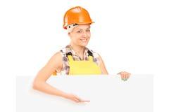 Kvinnligt anseende för manuell arbetare bak tom panel och att göra en gest Fotografering för Bildbyråer