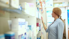Kvinnligt apotekareanseende på räknaren i apotek stock video