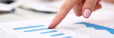Kvinnligt armpunktfinger i finansiell graf arkivfoto