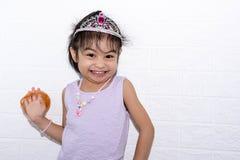 Kvinnligt asiatiskt posera för barnflicka som är knäpp, medan bära någon tillbehör som kronan, halsband och bära den purpurfärgad royaltyfri fotografi