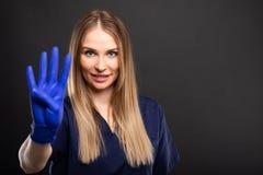 Kvinnligt bära för tandläkare skurar visningvisningen nummer fyra Royaltyfria Bilder