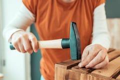 Kvinnligt bulta för snickare spikar in i träspjällådan arkivbilder