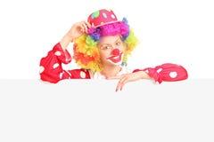 Kvinnligt clownanseende bak en tom panel Arkivbild