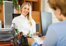Kvinnligt diskutera för kontorist och för klient royaltyfria bilder