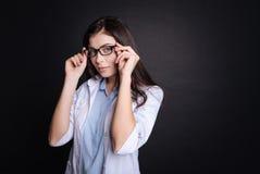 Kvinnligt doktorsanseende för angenäm professioanl på svart bakgrund arkivfoto
