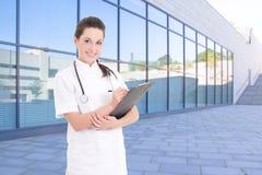Kvinnligt doktorsanseende mot modern sjukhusbyggnad arkivbild