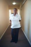 Kvinnligt doktorssjuksköterskaanseende i korridor arkivfoton