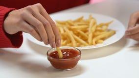 Kvinnligt doppa som är rikt i kalorier stekte potatisar in i tomatsås, genomdränkt fett stock video