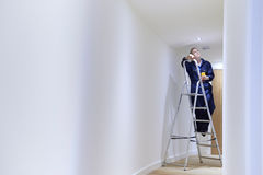 Kvinnligt elektrikerInstalling Lights In tak Royaltyfria Bilder