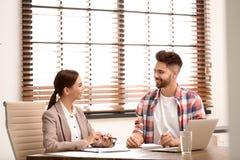 Kvinnligt försäkringmedel som konsulterar den unga mannen arkivfoto