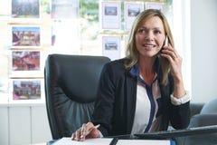 Kvinnligt fastighetsmäklareOn Phone In kontor royaltyfri fotografi