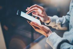 Kvinnligt finger som pekar på skärmen av mobiltelefonen på ljus för bokeh för bakgrundsbelysningglöd i den atmosfäriska natten Royaltyfria Foton