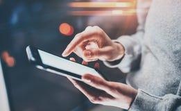 Kvinnligt finger som pekar på skärmsmartphonen på ljus för bokeh för bakgrundsbelysningglöd i den atmosfäriska natten horisontal Arkivbild