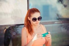 Kvinnligt flickasammanträde för kvinna i en bussstation genom att använda applikation på smartphonen för att kalla taxien Royaltyfri Fotografi