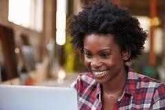 Kvinnligt formgivareUsing Laptop At skrivbord i modernt kontor Fotografering för Bildbyråer