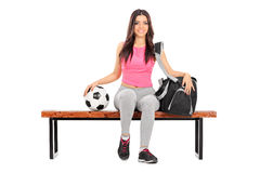 Kvinnligt fotbollsspelaresammanträde på en bänk Arkivfoto