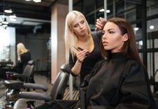 Kvinnligt frisöranseende och danandefrisyr till kvinnan i salong arkivbild