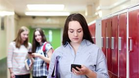 Kvinnligt högstadiumstudentBullied By Text meddelande i korridor lager videofilmer