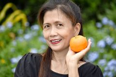 Kvinnligt högt och lycka med en apelsin arkivfoto
