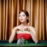 Kvinnligt hasardspelaresammanträde på kasinot bordlägger Royaltyfria Foton