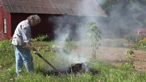 Kvinnligt högt trädgårdsmästarebrännskadagräs och avskräden i brand på äng i lantlig by inhyser gården 4K lager videofilmer