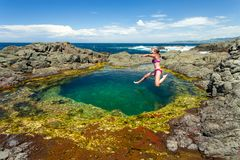 Kvinnligt hoppa in i sjösidan vaggar pölen arkivfoton