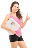 Kvinnligt innehav ett fjäll och ge upp en tum Arkivfoto