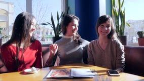 Kvinnligt kamratskap, unga kvinnor pratar och omfamnar i kafé på bakgrund av fönstret lager videofilmer