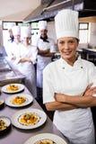 Kvinnligt kockanseende med armar som korsas i kök royaltyfri foto