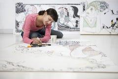 Kvinnligt konstnärDrawing On Large papper Royaltyfria Bilder