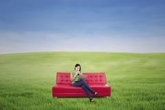 Kvinnligt koppla av på den utomhus- röda soffan Royaltyfria Bilder