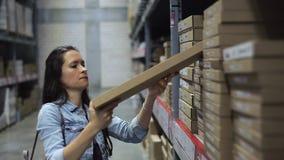 Kvinnligt kundk?pandegods f?r husrenovering i ett maskinvarulager Kvinna som söker efter ett köp på lagerlagret arkivfilmer