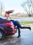 Kvinnligt lägger benen på ryggen från bilstammen Royaltyfri Bild