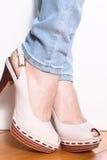 Kvinnligt lägger benen på ryggen i beige skor Royaltyfri Fotografi