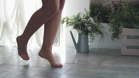 Kvinnligt lägger benen på ryggen nära övre flickan går barfota hemma lager videofilmer