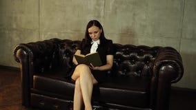 Kvinnligt läsa en bok på soffan Ståendekvinna20-tal genom att använda läseboken, medan vila och sitta på soffan i ljust lager videofilmer