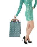 Kvinnligt långt lägger benen på ryggen i svart skor, och shoppinggåvan hänger lös. Royaltyfri Bild