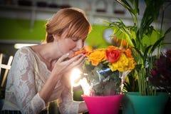 Kvinnligt lukta för blomsterhandlare steg blommor Arkivfoton