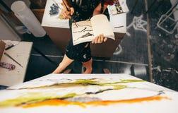Kvinnligt målaresammanträde i studion som gör en teckning Arkivbilder