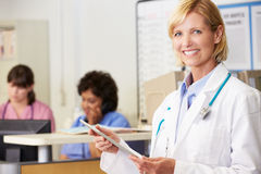 Kvinnligt manipulera genom att använda den Digital tableten på sjuksköterskor posterar Royaltyfria Bilder