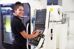 Kvinnligt maskineri för teknikerOperating CNC på fabriksgolv arkivfoton