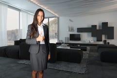 Kvinnligt medel Showing Thumbs upp på vardagsrummet royaltyfria foton