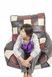 Kvinnligt modellsammanträde på den färgrika soffan med isolaten. Royaltyfri Bild